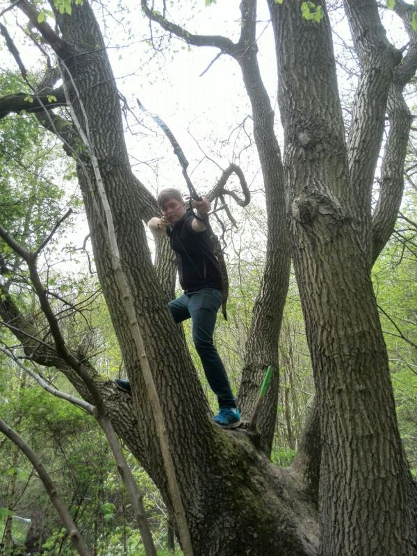 Recurveschütze Adrian Dinter zielt von einem Baum bei der 11. Hasselfelder Mai-Jagd 2015